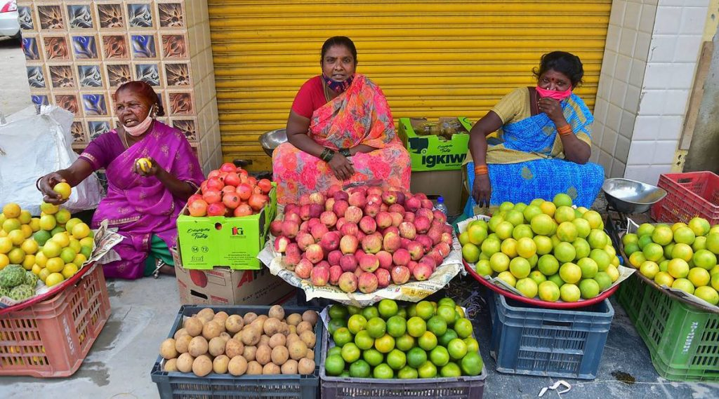 Roadside vendors selling fruits wait for customers, as coronavirus cases surge across the country, in Bengaluru. (PTI)